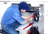 Un plombier qui répare un lavabo